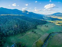 Aerial view of forested mountains, meadows, pastures, and rural road. Aerial view of forested mountains, meadows, pastures, and rural road Stock Image
