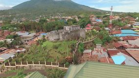 Aerial view of Fort Tolukko on tropical island Ternate with volcano, Indonesia. Aerial view of Fort Tolukko on tropical island Ternate with Gamalama volcano in stock video
