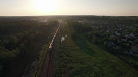 Aerial view of freight train in the country, Russia. Aerial shot of a cargo train traveling through the green countryside with summer houses. Sunset scene stock footage