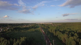 Aerial view of freight train running in the countryside, Russia. Flying over freight train running through the village. Scene with countryside in Russia stock video footage