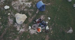 Aerial view friend have a campfire in the middle of mountain , and tent behind them , they have spending a good time stock video footage