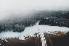 Aerial view of frosty forest road and fog above forest.  stock images