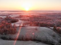 Aerial view of a frosty misty landscape at sunrise. With low rolling hills, woodland trees and a fiery sun rising over the horizon stock images