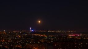 Aerial view full moon moving in dark sky over modern city. Timelapse sky night city stock video