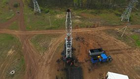Company Employees Work on Oil Rig against Forest
