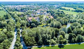 Aerial view of a German village with a small forest, a pond and a moated castle in the foreground stock photos