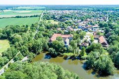 Aerial view of a German village with a small forest, a pond and a moated castle in the foreground stock photography