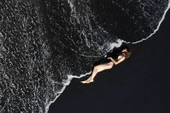 Aerial view of woman in swimsuit lying on black sand beach. stock photos