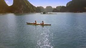 Aerial View Girl and Guy Row Backwards in Kayak and Islands. Aerial view girl guy rest and row backwards in kayak on bay water against floating farms and islands stock video