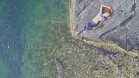 Aerial view girl lies on rocky beach against turquoise ocean stock footage
