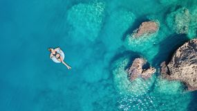 Aerial view at the girl on sea surface. Royalty Free Stock Photos