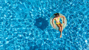 Aerial view of girl in swimming pool from above, kid swim on inflatable ring donut and has fun in water. On family vacation Stock Photo