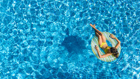 Aerial view of girl in swimming pool from above, kid swim on inflatable ring donut and has fun in water Royalty Free Stock Photography