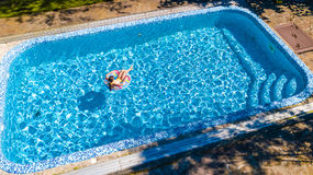 Aerial view of girl in swimming pool from above, kid swim on inflatable ring donut and has fun in water Stock Image