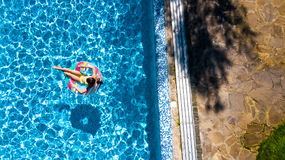 Aerial view of girl in swimming pool from above, kid swim on inflatable ring donut and has fun in water. On family vacation Royalty Free Stock Photo