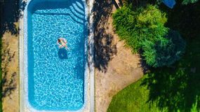 Aerial view of girl in swimming pool from above, kid swim on inflatable ring donut and has fun in water. On family vacation Royalty Free Stock Images