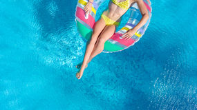 Aerial view of girl in swimming pool from above, kid swim on inflatable ring donut and has fun in water. On family vacation Stock Photos