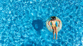 Aerial view of girl in swimming pool from above, kid swim on inflatable ring donut and has fun in water. On family vacation Stock Images