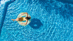 Aerial view of girl in swimming pool from above, kid swim on inflatable ring donut and has fun in water. On family vacation Royalty Free Stock Photography