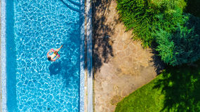 Aerial view of girl in swimming pool from above, kid swim on inflatable ring donut and has fun in water. On family vacation Stock Photography