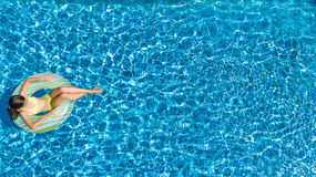 Aerial view of girl in swimming pool from above, kid swim on inflatable ring donut in water on family vacation. Aerial view of girl in swimming pool from above stock photo
