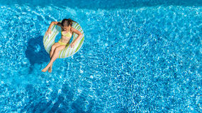 Aerial view of girl in swimming pool from above, kid swim on inflatable ring donut in water on family vacation. Aerial view of girl in swimming pool from above Royalty Free Stock Images