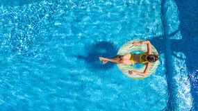 Aerial view of girl in swimming pool from above, kid swim on inflatable ring donut in water on family vacation. Aerial view of girl in swimming pool from above Stock Image