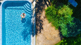 Aerial view of girl in swimming pool from above, kid swim on inflatable ring donut in water on family vacation. Aerial view of girl in swimming pool from above Stock Photography