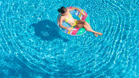 Aerial view of girl in swimming pool from above, kid swim on inflatable ring donut in water on family vacation. Aerial view of girl in swimming pool from above Royalty Free Stock Photo