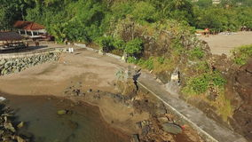 Aerial view of girl walking towards Pura Batu Bolong temple in Lombok, Indonesia stock footage