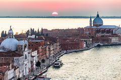 Setting red sun over the Giudecca island of Venice surrounded by stock photo