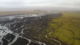 Aerial view of glacial rivers, river delta, black volcanic sand in south Iceland,  a green plain and a mountain in the distance, c