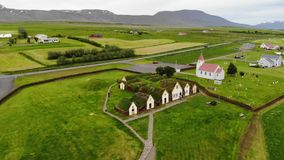 Aerial view Glaumbaer turf farm, Iceland. Historical Glaumbaer turf farm with grass on the rooftops, museum, church and surroundings, aerial shot, Varmahlid stock video