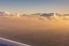 Aerial view of golden clouds lit by the evening sun over Florida, view from the aircraft during the flight. Royalty Free Stock Photos