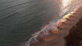 Aerial view golden sunset over the sea with waves crashing on the shore with beautiful reflections on the water and far away, one stock footage