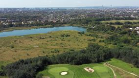 147 aerial view of golf course, city and ocean, 4k. Flying with drone above golf course in New York stock footage