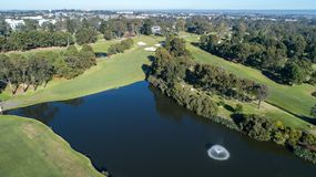 Aerial view of golf course dam with fountain surrounded by fairways, trees and bunkers. Aerial view of golf course water hazard dam with fountain surrounded by Stock Photos
