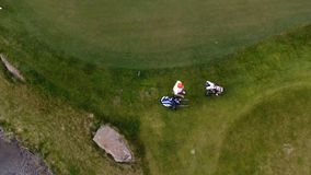 Aerial view Golf course. Golfers walking down the fairway on a course with golf bag and trolley royalty free stock photography