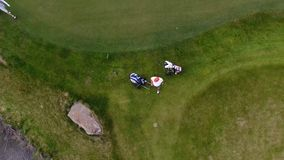 Aerial view Golf course. Golfers walking down the fairway on a course with golf bag and trolley stock footage