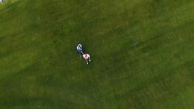 Aerial view Golf course. Golfers walking down the fairway on a course with golf bag and trolley stock video footage
