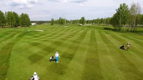 Aerial view golf course. Golfers walking down the fairway on a course with golf bag and trolley stock video
