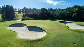 Aerial view of golf course green with sand bunkers on sunny day surrounded by trees Stock Images