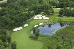 Aerial view of golf fairway and green with traps, pond and trees Stock Photo