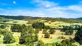 Aerial view on a golf field with green hills on the background. Waiheke Island, Auckland, New Zealand. Stock Photos