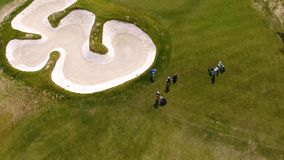 Aerial view of golfers playing on putting green. Professional players on a green golf course. Stock Photos