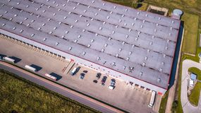 Aerial view of goods warehouse. Logistics center in industrial city zone from above. Aerial view of trucks loading at logistic cen Royalty Free Stock Images