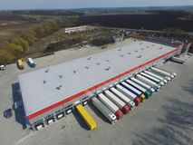 Aerial view of goods warehouse. Logistics center in industrial city zone from above. Aerial view of trucks loading at logistic center royalty free stock photos