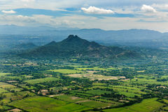 Aerial view of green cultivated fields in front of mountains on island of Roatan, Honduras Stock Images