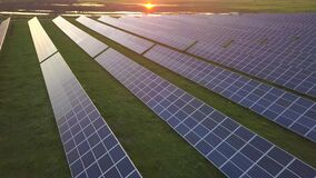 Aerial view of green field with solar energy panels for renewable electricity production.