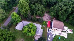 Aerial view of green forest treetops from above in air plane flight. Residential houses in dense forest from above overhead aerial view stock video footage